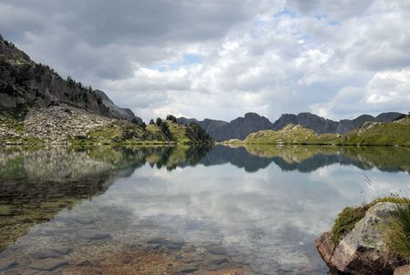 View of mountain lake with mountains and clouds in background Stock Photo