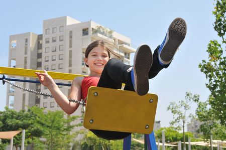 portret: Portret of a swinging girl on backgroung of sky and house Stock Photo