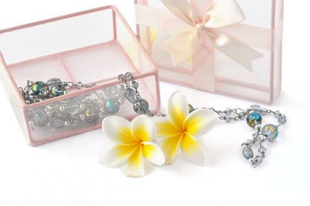 Composition of two flower, chain and gift box on white background. photo