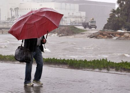 View of a man walking with umbrella under the rain.