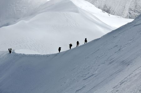 ice climbing: View of group hiking on slope of high Alps mountains.