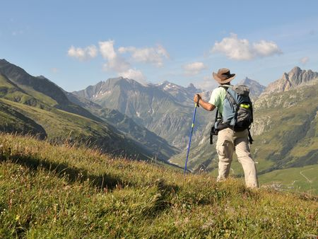 View of Alps mountains and a tourist standing on a footpath. Фото со стока