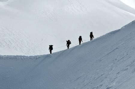 登る: アルプスの高い山の斜面上のハイキング グループのビュー。 写真素材