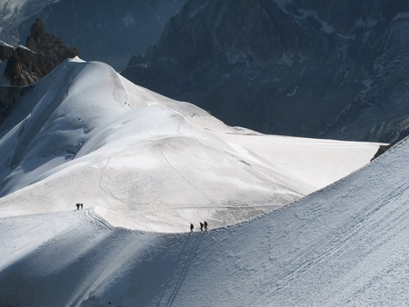 recreational climbing: View of high Alps and few mountaineers on a snow slope.