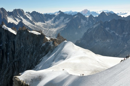 recreational climbing: View of a range of high Alps and few mountaineers on a snow slope. Stock Photo