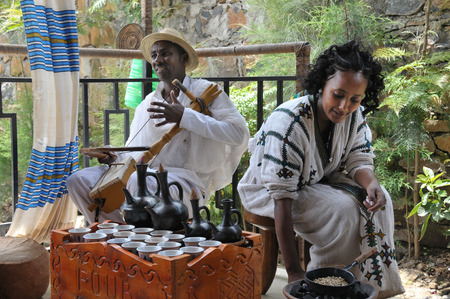 Axum, Ethiopia - September 28, 2012  Young Ethiopian woman in traditional clothing is preparing a traditional coffee ceremony  Man is playing on a masenqo  This ritualised ceremony is an important part of the Ethiopian culture