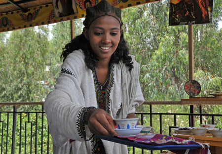 ethiopian: Axum, Ethiopia - September 28, 2012: Young Ethiopian woman in traditional clothing is serving coffee during a traditional coffee ceremony. This ritualised ceremony is an important part of the Ethiopian culture.