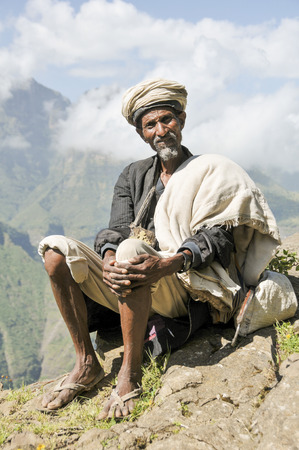 Simien national park, Ethiopia - October 03, 2012: Old Ethiopian man in traditional clothing is resting on a side of a footpath.