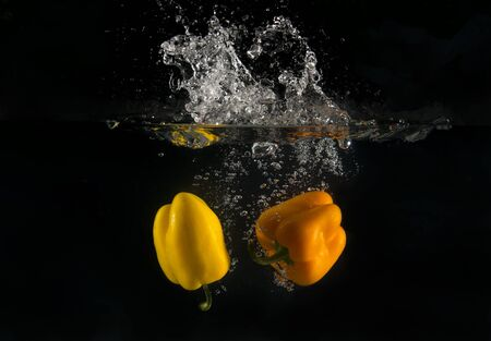 View of sweet peppers dropping into water on black background.