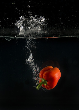 red pepper: View of sweet pepper droping into water on black background.