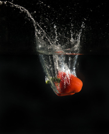 View of sweet pepper dropping into water on black background. Stock Photo