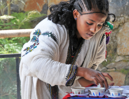 Axum, Ethiopia - September 28, 2012: Young Ethiopian woman in traditional clothing is serving coffee during a traditional coffee ceremony. This ritualised ceremony is an important part of the Ethiopian culture.
