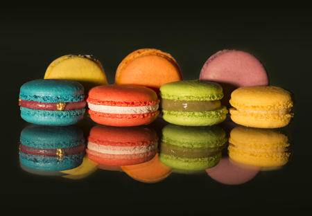 View of colorful macaroons and their reflections on black background Фото со стока