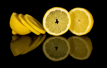 View of macro still life - cut lemon on black background with reflection