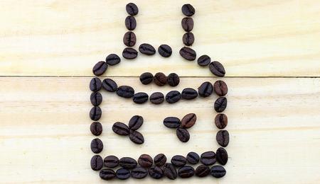 tomando refresco: granos de caf� con forma de la torta en el fondo de madera Foto de archivo