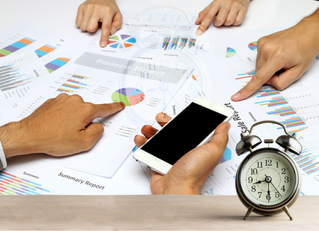 race for time: Business people hands analyst team work group during discussing financial review at early morning or Overtime in evening race against time,Alarm clock on wood for time concept