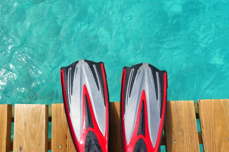 Red rubber fins on the pier over the blue tropical sea Stock Photo