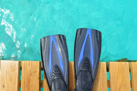 Blue scuba fins on the wooden pier over the blue ocean. Stock Photo