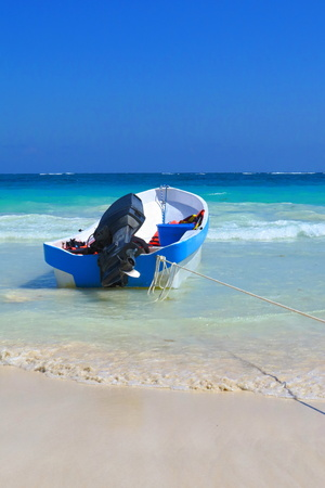 Colorful small boat on the beach with blue ocean in background. White sandy tropical beach with small colorful boat. Blue ocean with waves.