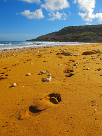 Footsteps in the red sandy beautiful empty beach. White clouds, blue sky and ocean in background. Gozo red sandy beach. Tropical empty shoreline with fine sand. Stock Photo