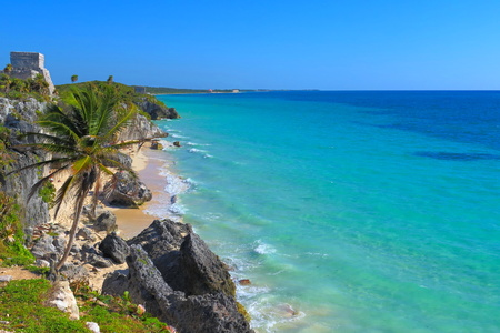 Mexican mayan temple in Tulum made from the limestone, close to the beautiful tropical caribbean sea. White fine sandy beach with palm trees, azure water. Stock Photo