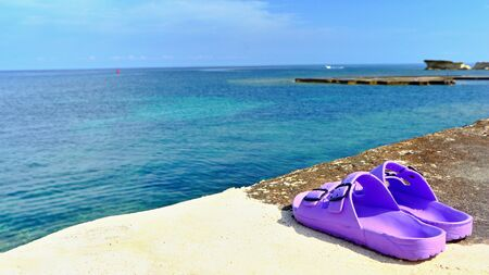 Purple vacation slippers, flip flops on the edge of the azure pristine sea. Calm scene, water surface, blue sky and sunny day.
