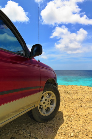 Off road red vehicle on the yellow tropical beach. Car looking on the sea, azure calm sea surface. Bright colors, white clouds, sunny day, serene beach holiday scene. Stok Fotoğraf