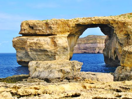 Maltese famous Azure window arch stone monument nearby the Blue Hole before collapsing into the sea. Blue water and yellow rocks and stones on Island of Gozo. Shore of Dwejra - Dwejra Window.