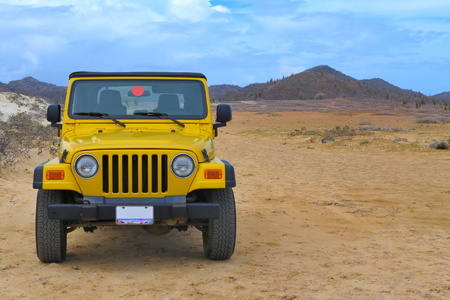 Yellow off-road car in a dry national park desert. Sandy dunes and hills under the blue sky. Sunny day on a tropical exotic vacation.