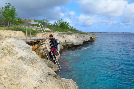 Scuba diver on the steel ladder coming out from the sea. Rocky coastline with scuba diver in diving equipment. Scuba diver on the tropical vacation coming from the water.