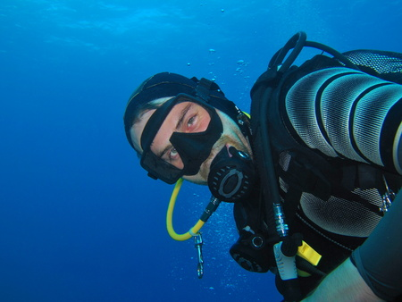 Happy scuba diver underwater portrait.
