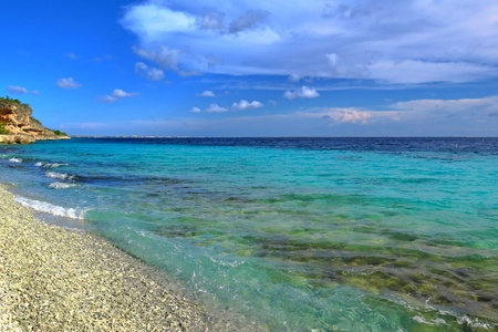 Exotic tropical pebble beach with calm azure ocean. Stok Fotoğraf
