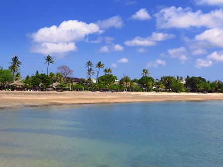 Exotic beach with calm blue sea, sand and palm trees. 免版税图像
