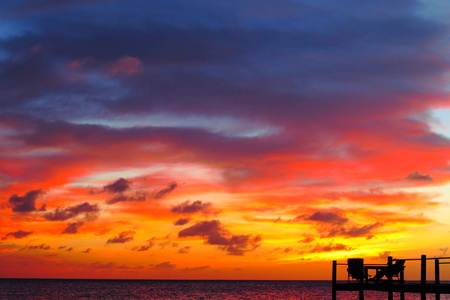 Sunset wooden pier with ocean, clouds and colorful sky. 免版税图像