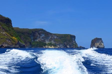 Remote coastline with the blue ocean and waves from boat.