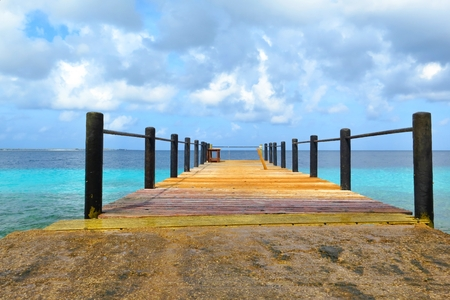 Tropical wooden pier leading to the azure exotic sea. 免版税图像