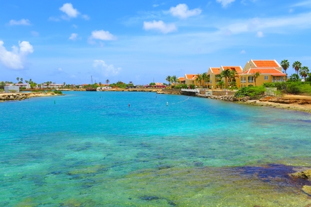 Beautiful exotic vacation lagoon with azure calm sea, palm trees and colored houses.