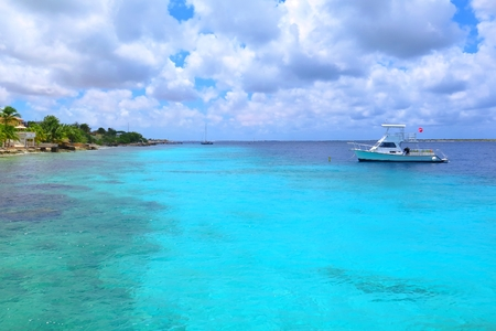 Azure cyan calm tropical sea with beautiful pebble shore and scuba diving ship. 免版税图像