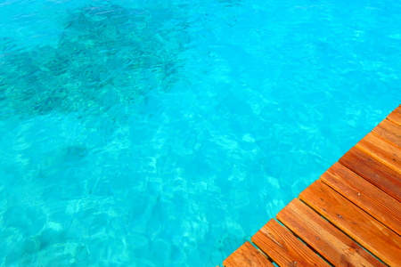 Azure cyan calm sea surface with wooden pier.