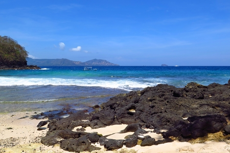 Tropical sandy beach with dark stones, small ship on the blue sea.
