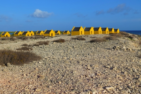 Yellow historical slave stone huts on the pebble exotic beach.