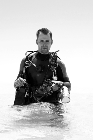 Scuba diver photographer prepared to go scuba diving, with equipment and underwater camera.