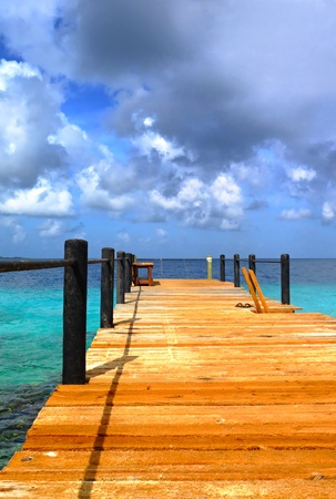 Wooden swimming pier in the tropical vacation resort under the big clouds. Turquoise calm water in exotic paradise island.