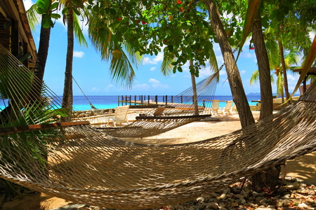 Hammocks for relaxing under the green palm trees with view on tropical azure sea. Stok Fotoğraf