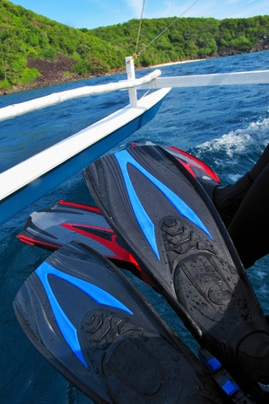 Red and blue fins above sea water. Two pairs of scuba diving fins on the traditional banka boat heading to the green tropical island.