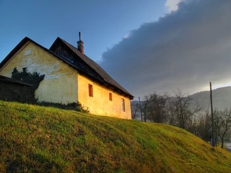 Abandoned house on the small grass hill. Golden light and dark dramatic clouds before a storm.