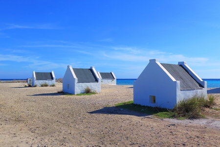 Tropical sandy beach with small white houses, slave huts. 免版税图像 - 98975677