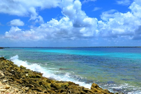 Stone seashore, pleasant waves and azure sea around island. Blue tropical sky with white clouds, sun shining.