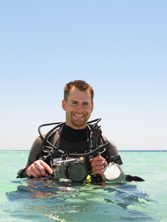 Portrait of smiling scuba diver photographer holding his underwater camera with strobe in tropical lagoon. Man ready to go diving. Part of diver's body is in azure sea, part is above water surface.