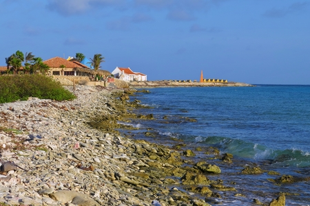 Tropical pebble beach with small slave houses and calm blue sea.